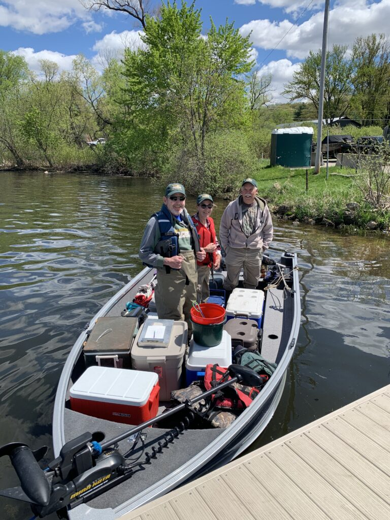 from left to right, Dave Marshall, Sue Marcquenski, and Tim Larson, in Tim's boat full of coolers of starhead topminnows ready for stocking in Lake Wisconsin on May 5, 2021